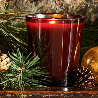 Lit candle in red glass vessel