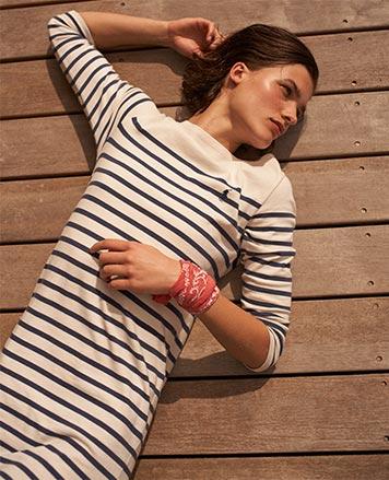 Woman lies on dock in navy-striped jersey dress