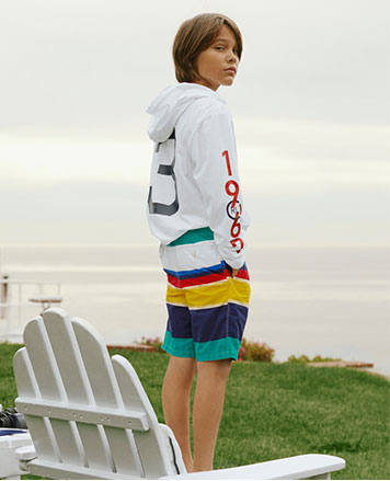 Boy wears multicolored striped shorts and white graphic sweatshirt.