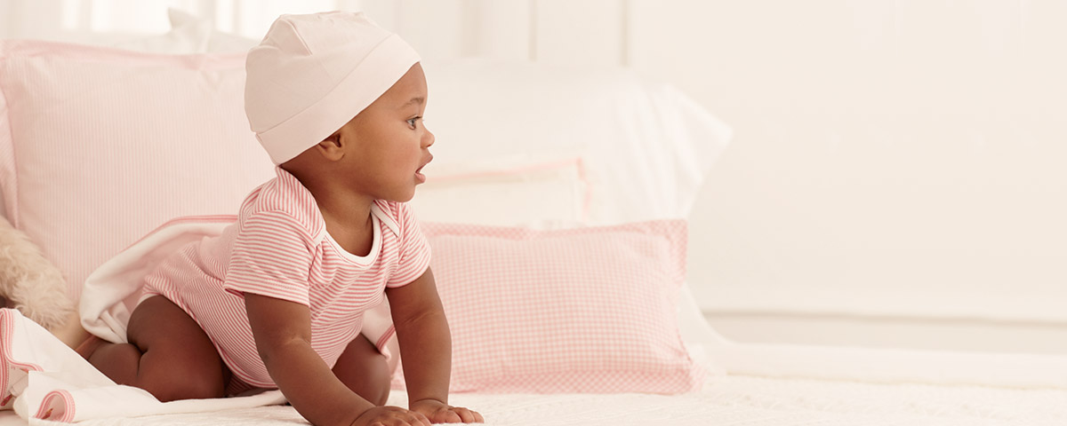 Baby wears pink-and-white striped one-piece and light pink hat.