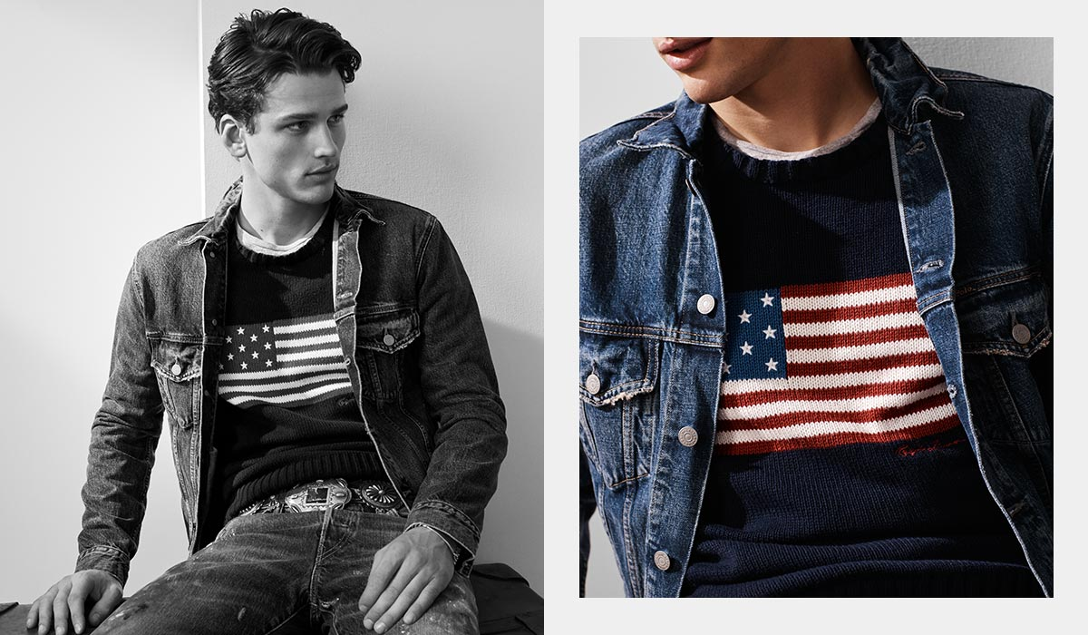 Model in denim jacket over navy sweater with American flag motif