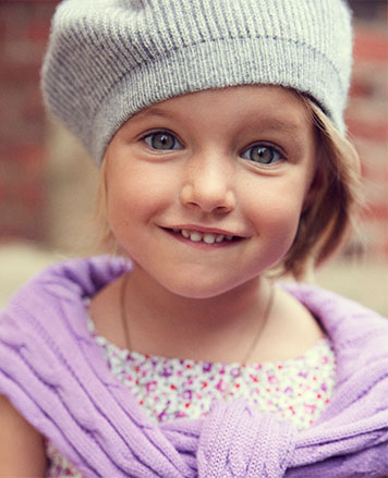 Girl wears lavender sweater tied around shoulders and grey knit hat.