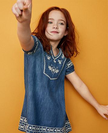 Girl wears embroidered denim dress.