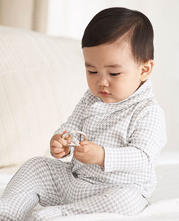 Baby boy wears grey houndstooth coverall.