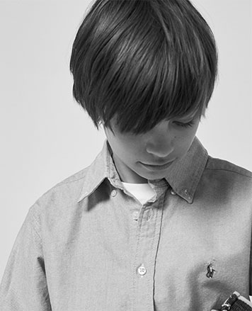 Black-and-white image of boy wearing button-down shirt.