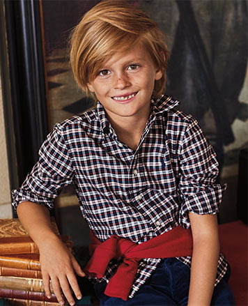 Boy wears checked button-down shirt with red sweater tied around waist.