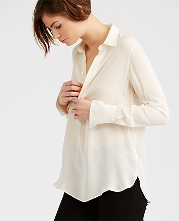 Model in cream silk georgette blouse with concealed buttoned half-placket