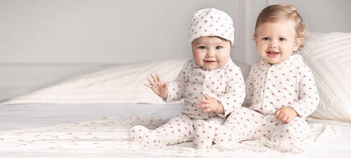 Babies wear reindeer-print onesies and a beanie.