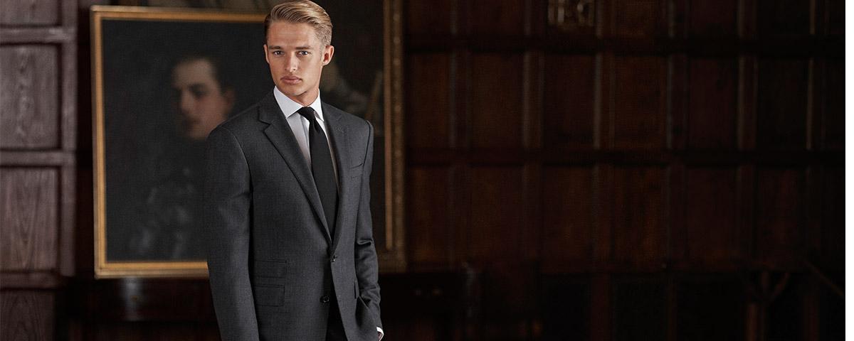 Man in sleek black suit in dark room