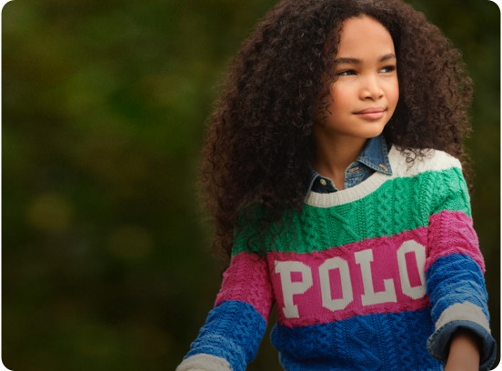 Girl in multicolored striped Polo logo sweater.