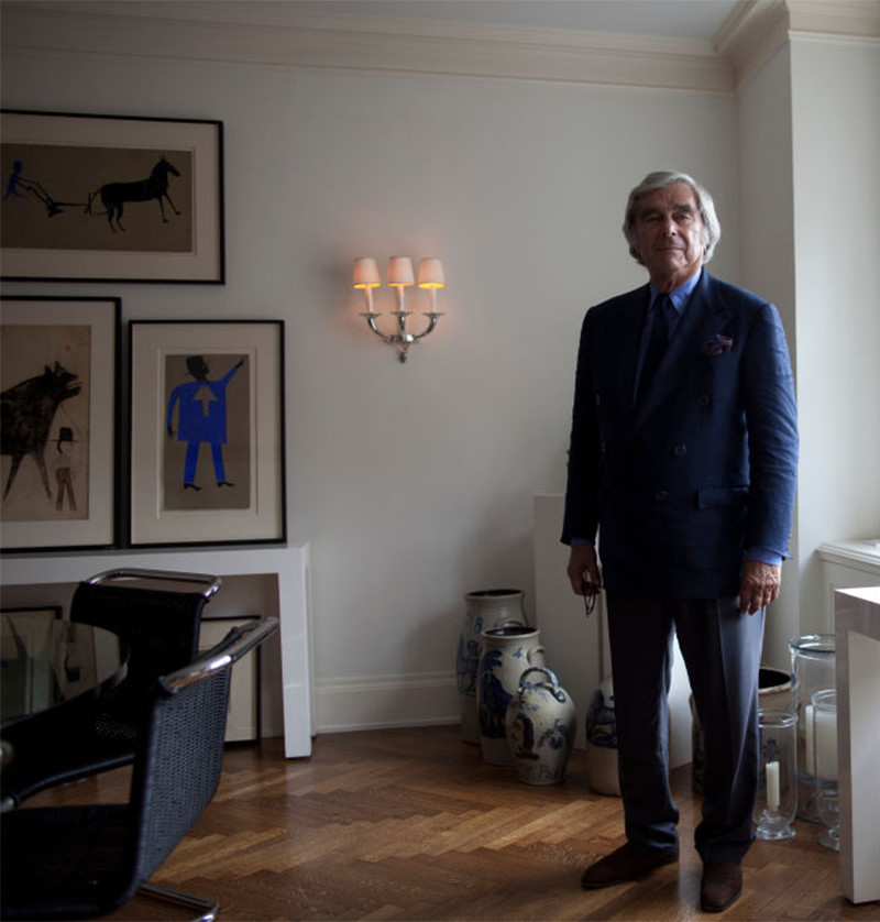 Jerry Lauren in his Manhattan apartment with a selection of Traylor's works on the wall behind him