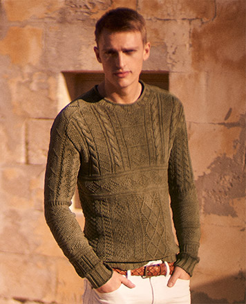 Man in olive sweater with various patterns