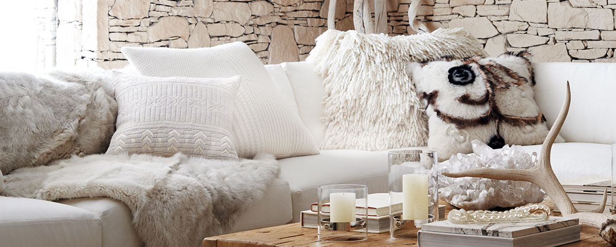 White couch covered in tonal throw pillows and blankets of various textures