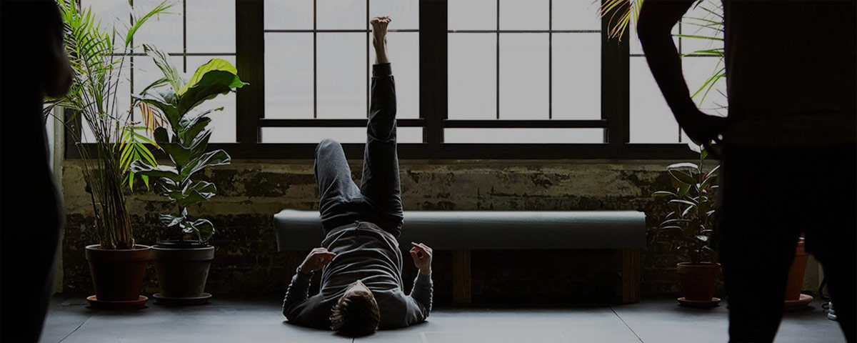 Photograph of man stretching on back in gym