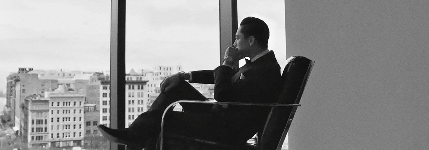 Man in suit sitting in chair looking out of window
