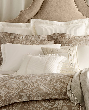 Bed appointed with neutral-hued sheeting with a 19th-century damask pattern