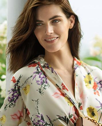 Woman wears floral-print top.