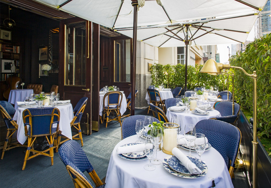 Patio with blue wicker chairs & tables with white tablecloths