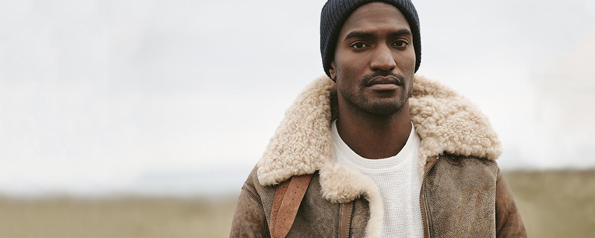 Man in shearling jacket & black knit hat