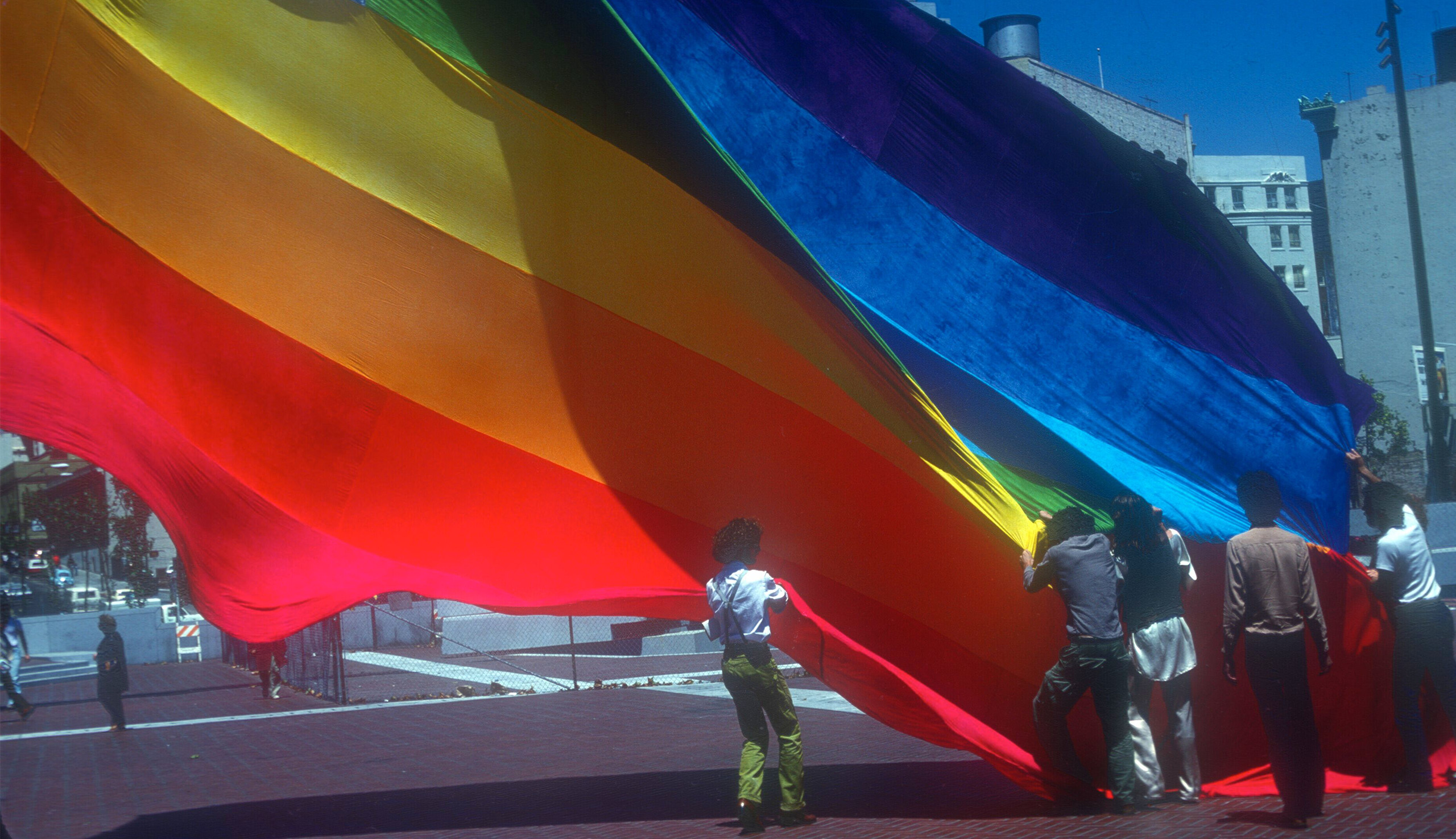 Gilbert Baker and volunteers raising the original Pride flag in San Francisco's United Nations Plaza in 1978