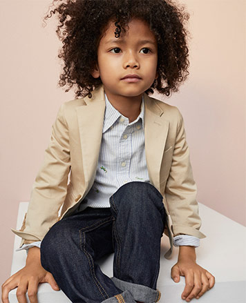 Boy wears tan sport coat over button-down and jeans.