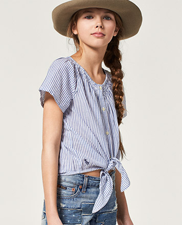 Girl wears striped tie-front top, jean shorts, and a sun hat.