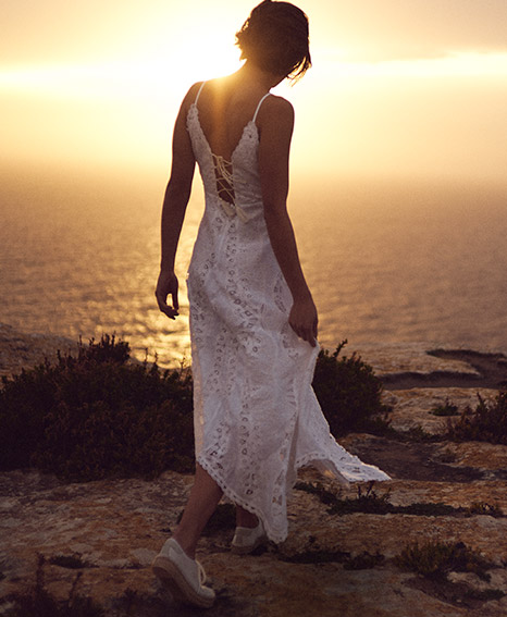 Woman on beach in white eyelet linen maxidress