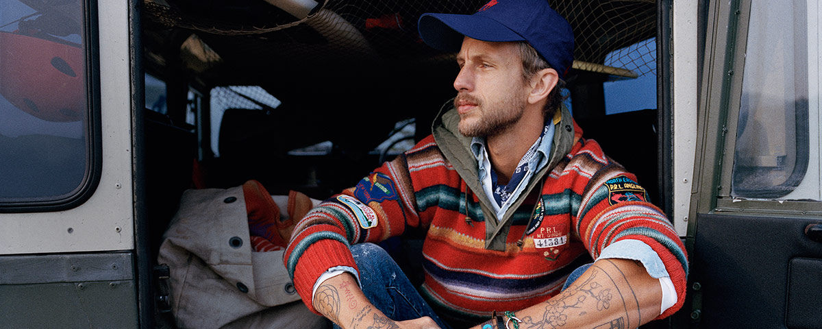 Man in vibrant striped pullover with outdoors-inspired patches