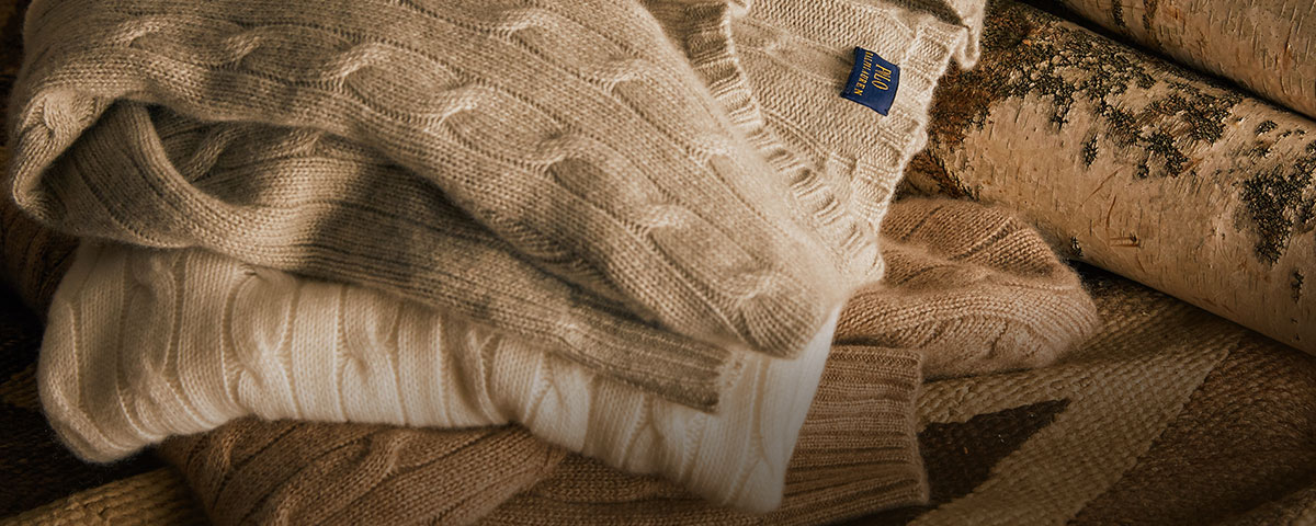 Stack of neutral-hued cable-knit cashmere sweaters