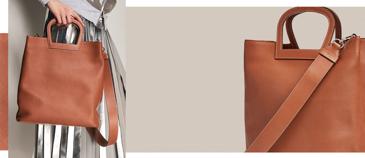 Golden brown leather tote bag with horseshoe-shaped top handles