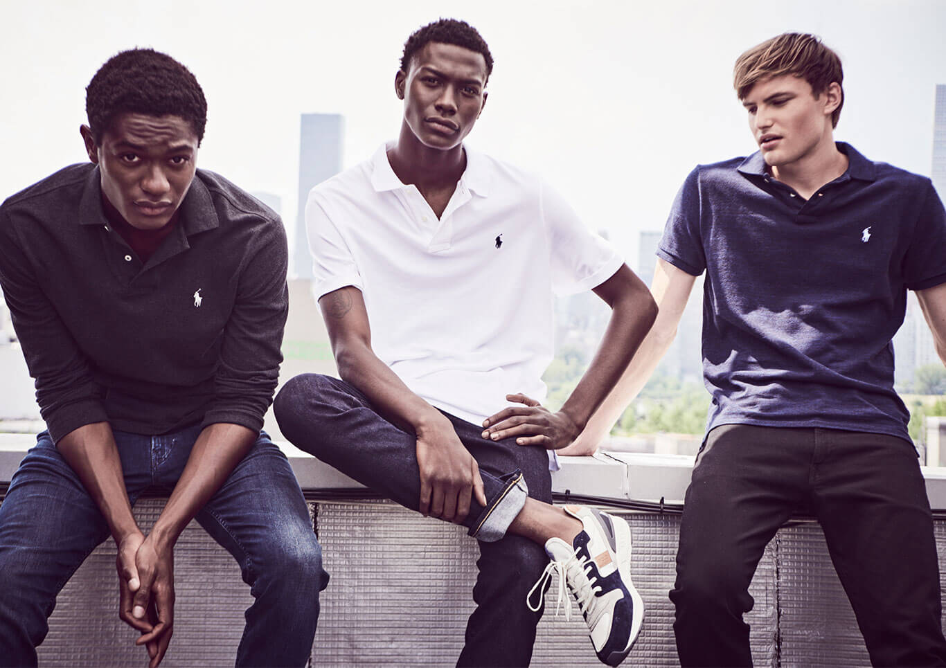 Three men on rooftop in black, white & navy Polo shirts