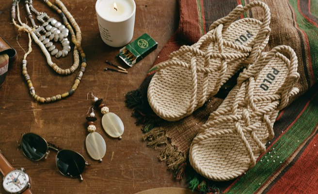 rope sandals and accessories on wooden table.