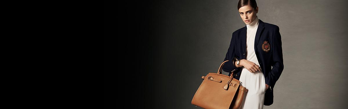 Woman in cream trousers & blazer holding large RL50 handbag