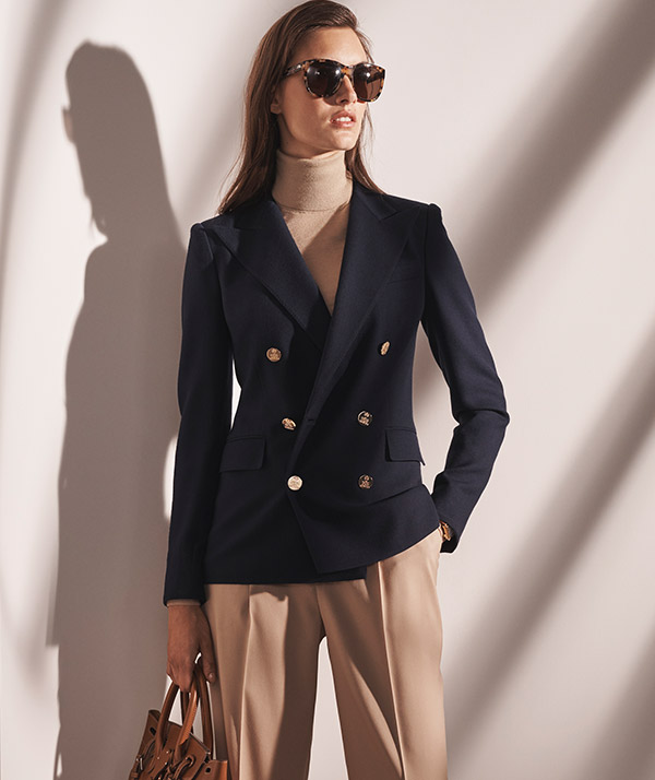 Woman wears navy blazer with gold-tone buttons