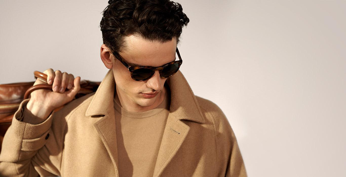 Man in round tortoiseshell sunglasses & camel coat