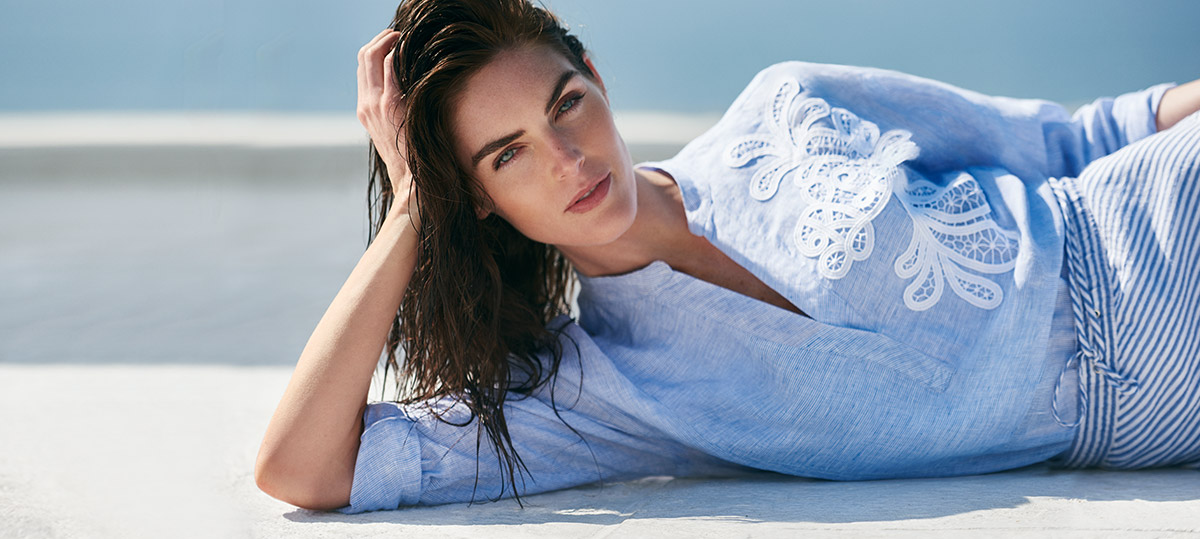 Model Hilary Rhoda in lace-embroidered blue top with split neckline