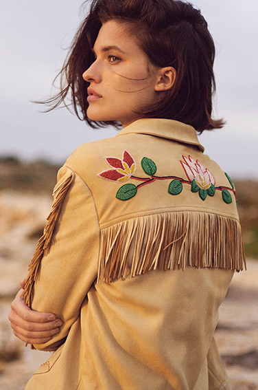Woman in tan suede jacket with fringe & embroidery