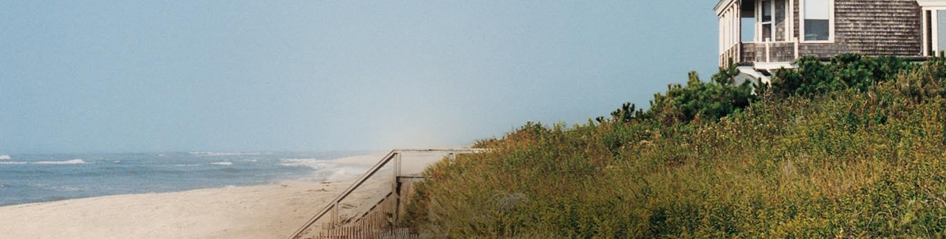 Photograph of sandy beach and beach house.