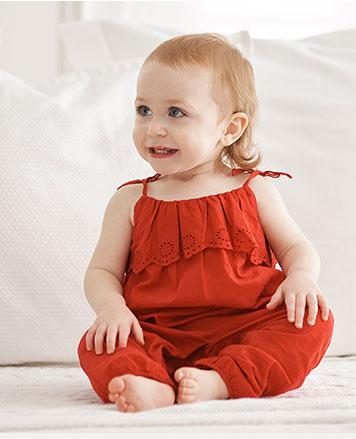Baby girl wears red eyelet romper.