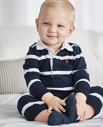 Baby boy wears navy-and-white striped coverall.