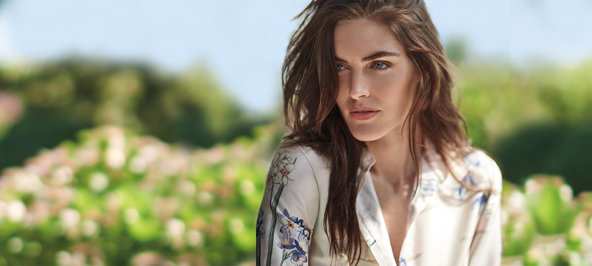 Model Hilary Rhoda in field wearing floral buttoned blouse