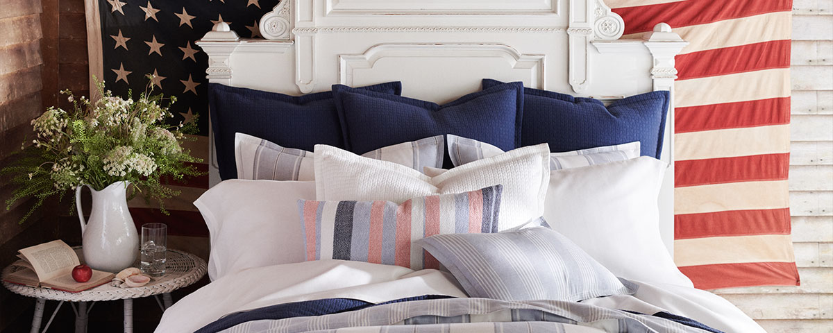 Bed appointed with sheeting in an Americana-inspired palette