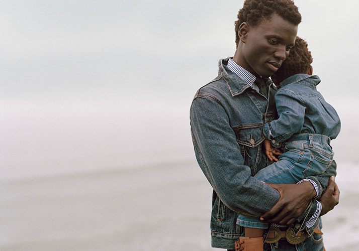 Father in denim jacket carrying toddler son, also dressed in denim