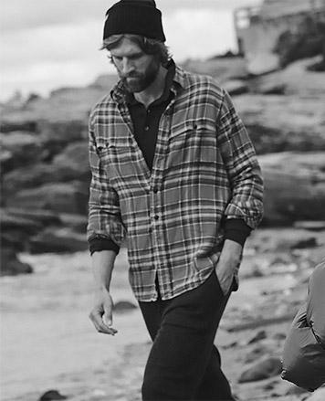 Man in plaid shirt walks on beach