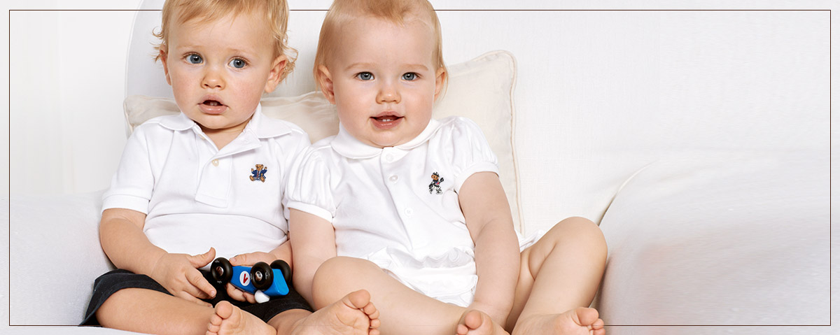 Baby boy and girl in white Polos with embroidered bear at chest