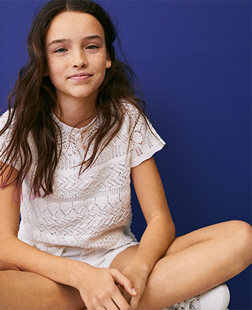 Girl wears short-sleeve white shirt with white shorts.