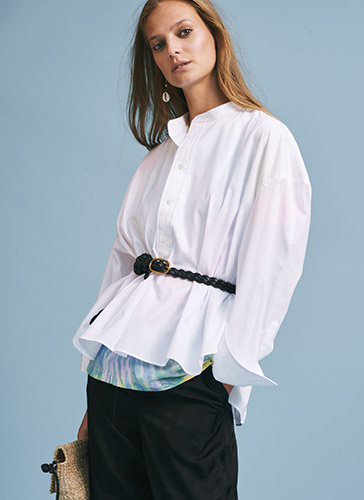 Woman in white peplum blouse with band collar & buttoned placket