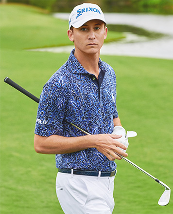 db984ba66 Golf player on green in Polo shirt with abstract leaf print
