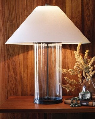 Lamp with glass base and white shade on wooden table.