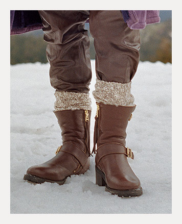 Woman wears brown leather boots with belt accent